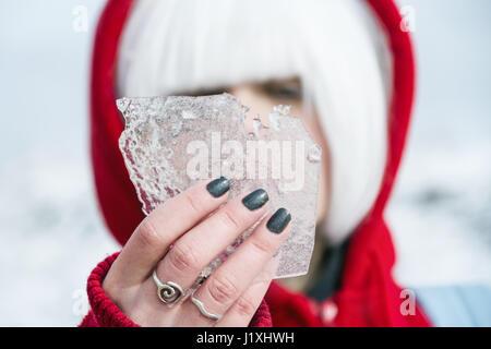 Jeune femme avec capuche rouge et cheveux blancs en hiver Banque D'Images