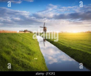 Les moulins à vent au lever du soleil. Paysage rustique néerlandaise avec moulins à vent près de l'eau des canaux, Banque D'Images
