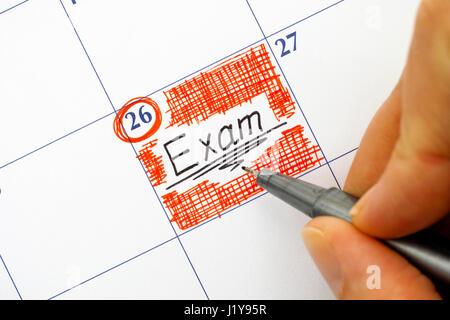 Femme doigts avec stylo noir écrit Examen de rappel dans le calendrier. Banque D'Images