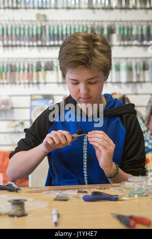 Un élève de l'école des adolescentes qui travaillent à temps partiel dans son magasin de bijoux. Banque D'Images