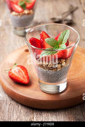 Petit déjeuner santé diète. chia pudding, des fraises et du muesli dans un verre , des fraises fraîches sur fond Banque D'Images