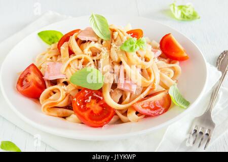 Tagliatelle avec du jambon, sauce tomate, tomates cerise et les feuilles de basilic sur plaque blanche - tagliatelles Banque D'Images