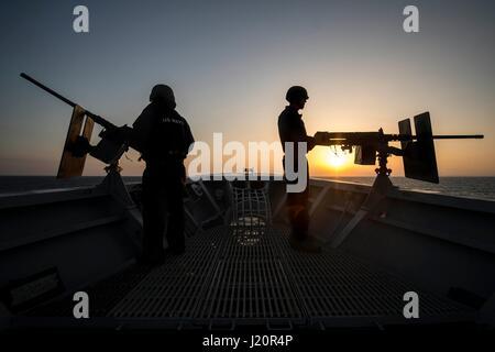 Les marins de la Marine américaine se profilent par le coucher de soleil comme ils l'homme mitrailleuses de calibre .50 à bord sur l'arc de la marine américaine de classe Ticonderoga croiseur lance-missiles USS Vella Gulf 7 juillet 2014 dans la mer Egée. (Photo par Edward Guttierrez III /US Navy par Planetpix)