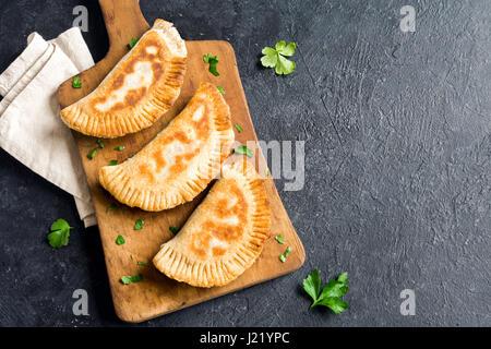 Des Samosas aux légumes frits (galettes, burekas) sur fond noir rustique - pâtisseries frites végétariennes pour Banque D'Images