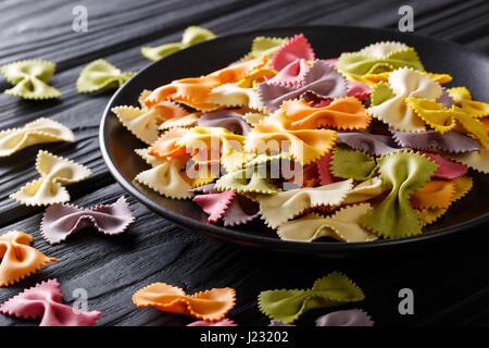 Matières premières italiennes pâtes farfalles multicolores close-up sur la table horizontale. Banque D'Images