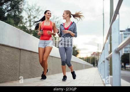 Beau paysage de deux femmes poursuivant leur activité à l'extérieur du jogging dans la ville à la tombée de la Banque D'Images
