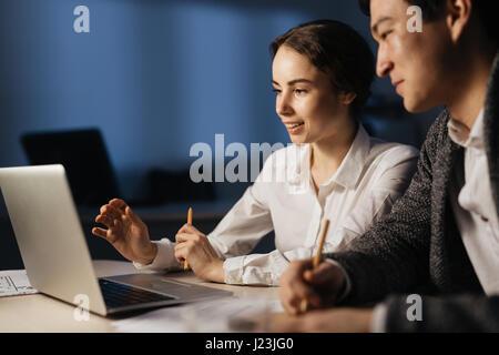 Les commerçants en ligne d'informations modernes discuter tard le soir Banque D'Images
