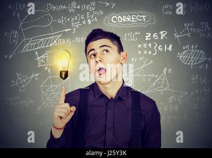 Smart student avec idée lumineuse ampoule et mathématiques et sciences des formules sur fond noir Banque D'Images