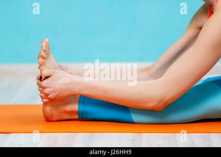 Woman doing yoga exercices sur tapis dans le hall Banque D'Images