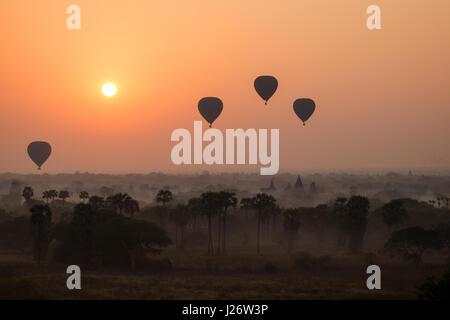 Silhouette de ballons à air sur la plaine de Bagan au lever du soleil au Myanmar (Birmanie). Banque D'Images