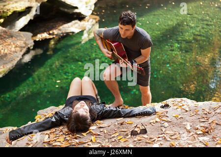 Jeune homme son amie sérénade par un ruisseau Banque D'Images