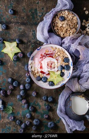 Bol à smoothie déjeuner sain. Yogourt aux fraises avec des bleuets, granola, menthe, pichet de lait et carambole Banque D'Images