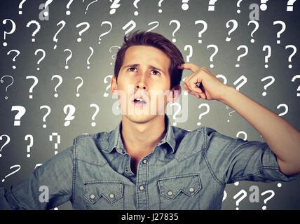 Bel homme confus réfléchie a trop de questions et pas de réponse se gratte la tête Banque D'Images