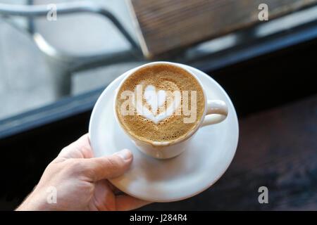 Cropped hand holding cappuccino avec forme de coeur art Banque D'Images