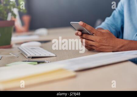 Jeune designer la lecture de messages texte à son bureau 24 Banque D'Images