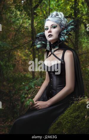 Portrait de jeune fille gothique dans les bois, vêtue de son corset et le collier de plumes. Banque D'Images