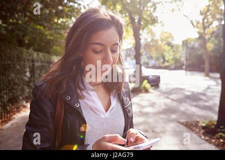 Young woman standing in street en utilisant un téléphone mobile, l'arrière allumé close up