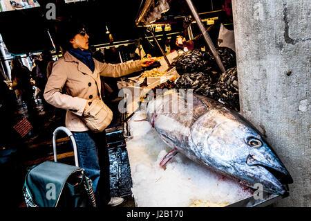 Femme acheter un poisson à côté de thon massive dans le marché du Rialto à Venise, Italie Banque D'Images