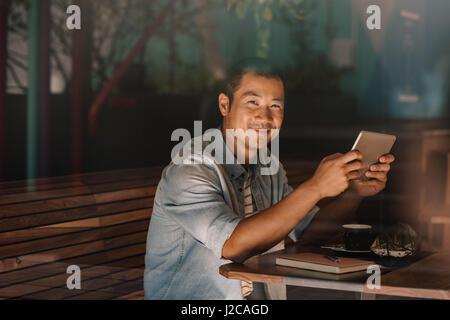 Smiling Asian man la navigation en ligne tout en restant assis dans un café Banque D'Images