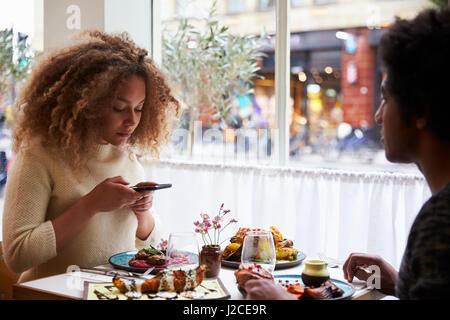 La prise de photo de Blogger alimentaire repas au restaurant sur Mobile Banque D'Images