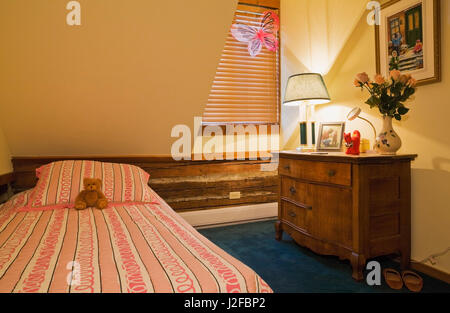 Lit simple et commode ancienne en bois dans la chambre de l'enfant sur le plancher à l'étage dans un style chalet Banque D'Images