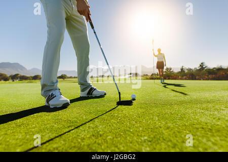 Low angle view of golfeur sur putting green sur le point de prendre la photo. Homme joueur de golf putting on vert Banque D'Images