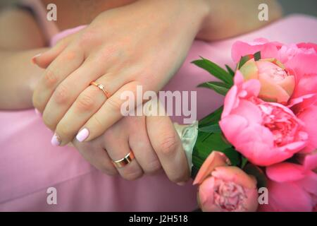Femme avec un bouquet de fleurs hugging her husband Banque D'Images
