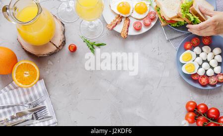 Table du petit déjeuner avec des œufs, du bacon, des tomates cerises, des sanwiches, jus d'orange Banque D'Images