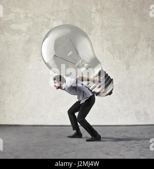 Businessman carrying immense lightbulb Banque D'Images