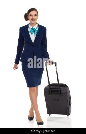 Femme en costume bleu avec sac voyage à roulettes à marcher en direction de la caméra. Vue de face. Studio pleine Banque D'Images