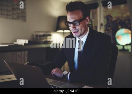 Smiling businessman working on laptop in office de séance de nuit à concentrés Banque D'Images