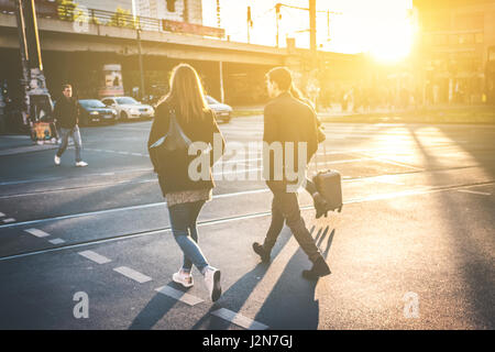 Couple walking on street - couple crossing street pendant le coucher du soleil Banque D'Images