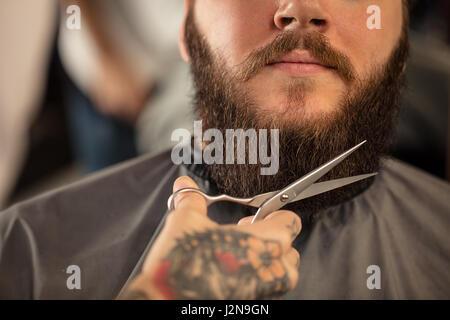Avec des ciseaux de coiffure homme barbu de rasage Banque D'Images