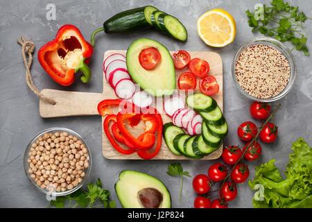 Ingrédients pour un bol bouddha: le quinoa, pois chiches, les légumes frais sur fond de béton gris. Vue de dessus Banque D'Images