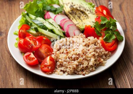 Bol bouddha avec mélange de légumes, quinoa sur fond de bois Banque D'Images