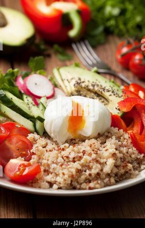 Bol bouddha avec mélange de légumes, quinoa et œuf poché sur fond de bois Banque D'Images