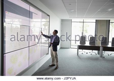 African American male architect working at large écran tactile dans la salle de conférence Banque D'Images