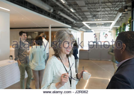 Smiling businesswoman networking, parler à businessman in office lobby Banque D'Images