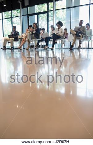 L'auditoire de la conférence en prenant des notes dans des chaises dans office Banque D'Images