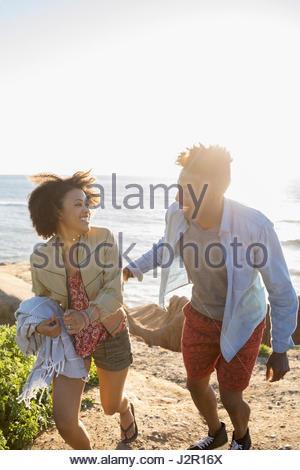 Jeune couple ludique walking on sunny beach Banque D'Images