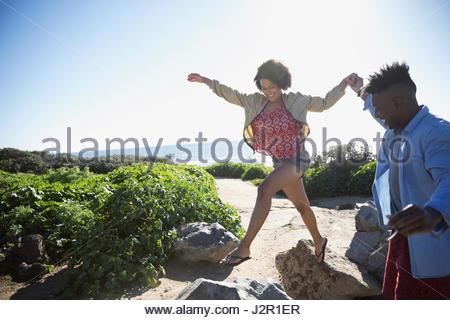 Jeune couple ludique sur des rochers sur la plage ensoleillée Banque D'Images