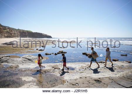 La famille Latino marche sur craggy sunny beach Banque D'Images
