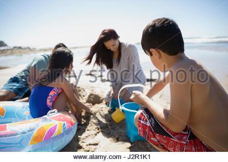 La famille Latino décisions sandcastle sur sunny beach Banque D'Images