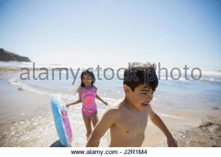 Frère et sœur latino avec anneau gonflable sur sunny beach Banque D'Images