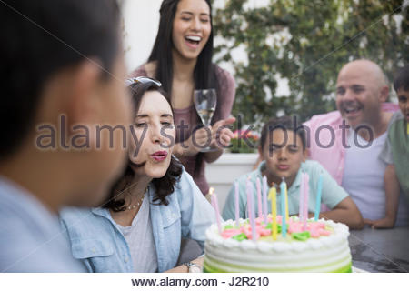 Multi-generation family celebrating birthday, blowing out candles on cake Banque D'Images