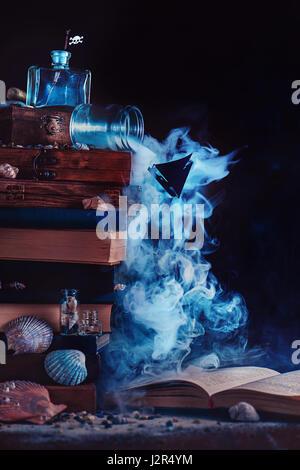 Marine sombre vie toujours avec un livre ouvert et un bateau silhouette dans une cascade de fumée Banque D'Images