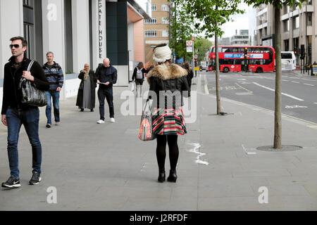 Trendy young woman walking along Aldgate High Street à Whitechapel dans East London EC3 UK KATHY DEWITT Banque D'Images