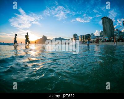 RIO DE JANEIRO - le 2 février 2013: Silhouettes passent devant le coucher du soleil sur la rive de la plage d'Ipanema. Banque D'Images