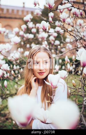 Jeune jolie fille se détendre dans le magnifique jardin. Magnolias rose fantastique Banque D'Images