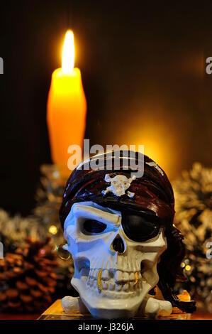 Crâne de pirate et une bougie allumée sur la table Banque D'Images